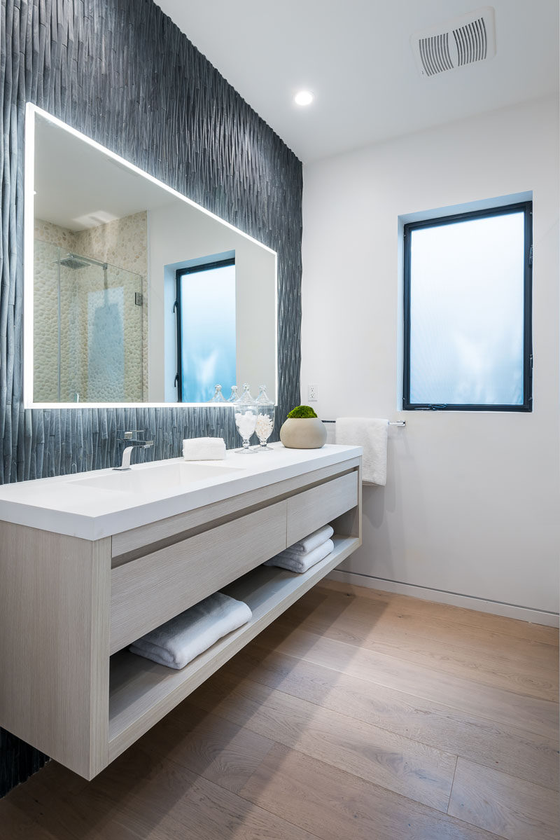 In this modern bathroom three dimensional grey tiles have been used to create an accent wall, while a backlit mirror highlights the design of the wall. #ModernBathroom #BathroomAccentWall #BacklitMirror