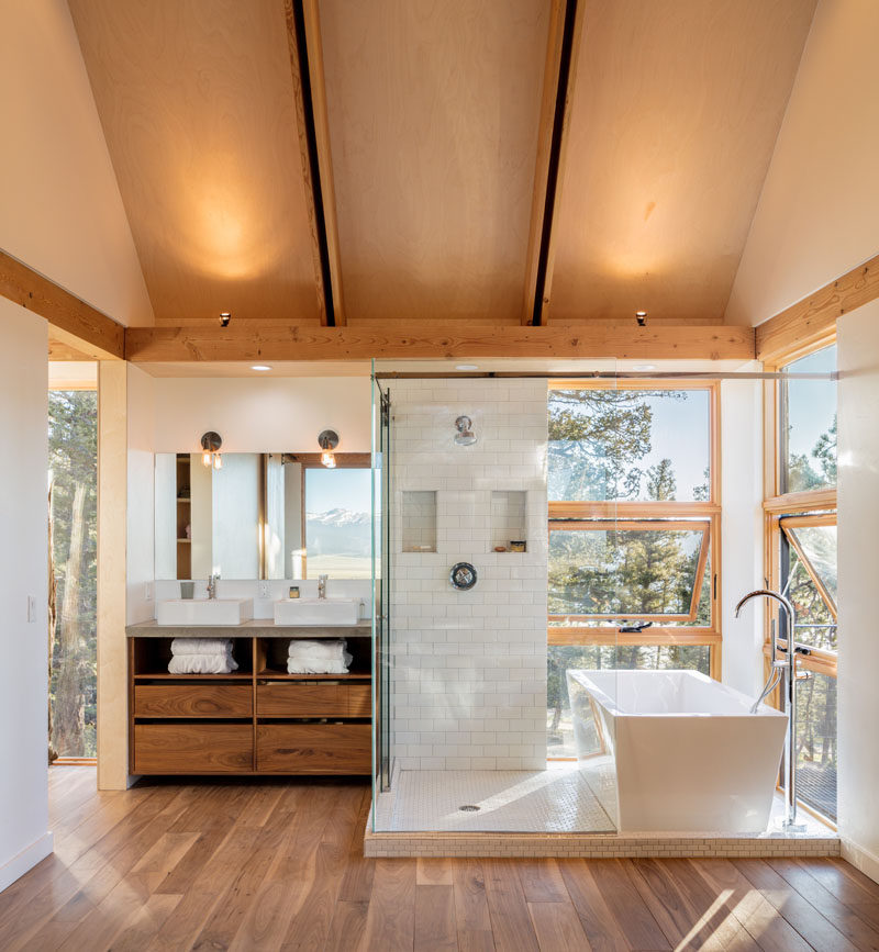 This modern and open bathroom has a glass-enclosed shower that sits next to a freestanding bathtub with views of the trees. #Bathroom #ModernBathroom #GlassEnclosedShower