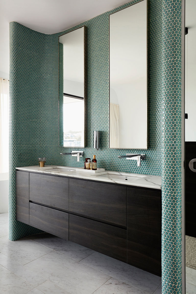 In this modern bathroom, green penny tiles have been used to create an accent wall behind the tall mirrors and vanity. #PennyTiles #TileAccent #Bathroom