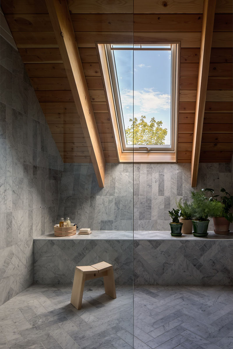 This modern bathroom has a window for views of the treetops and a Douglas fir ceiling brings a natural element inside. #Bathroom #GreyTile #Window