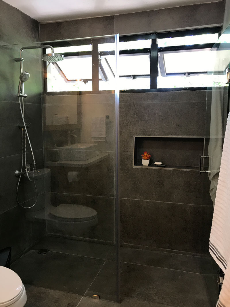 This renovated bathroom has glass shower surround and three outward opening windows at the top of the shower, that allow the light to travel throughout the small space. #UpdatedBathroom #GlassShowerSurround