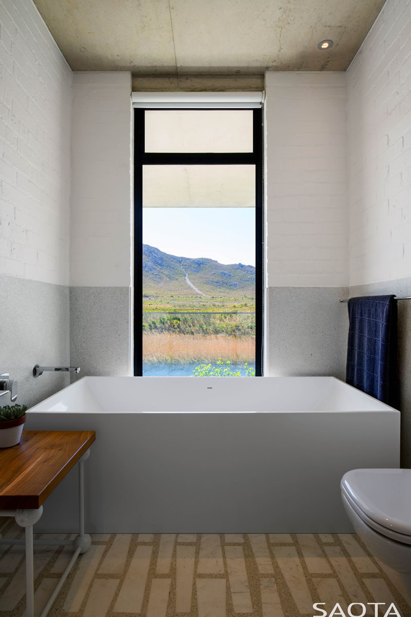 In this modern bathroom, the bathtub sits at one end of the room and a vertical window frames the view like artwork. #ModernBathroom #BathroomDesign
