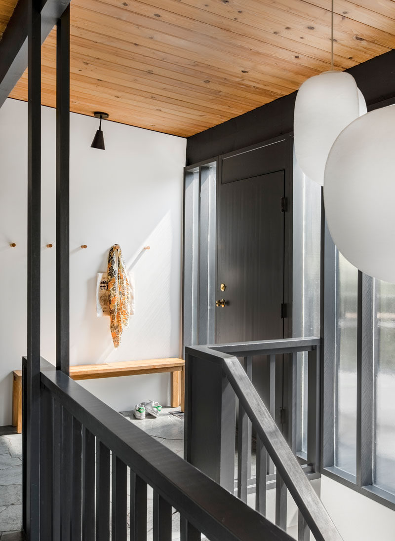 A black front door welcomes you to the home, that features a wood ceiling and exposed beams. #BlackFrontDoor