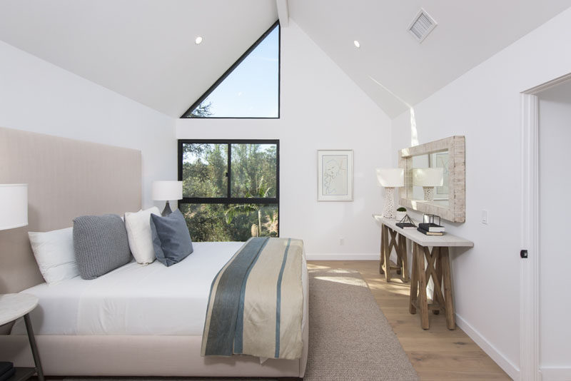 This contemporary bedroom features a vaulted ceiling, and a triangular window that draws your eye upwards to the height of the room.