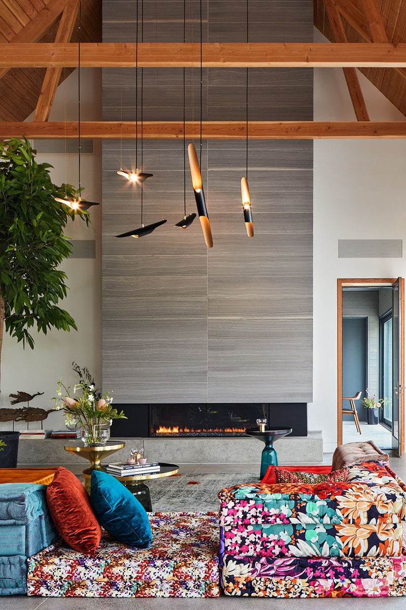 This modern living room has a brightly colored couch that's focused on the limestone fireplace. #ModernLivingRoom #Fireplace