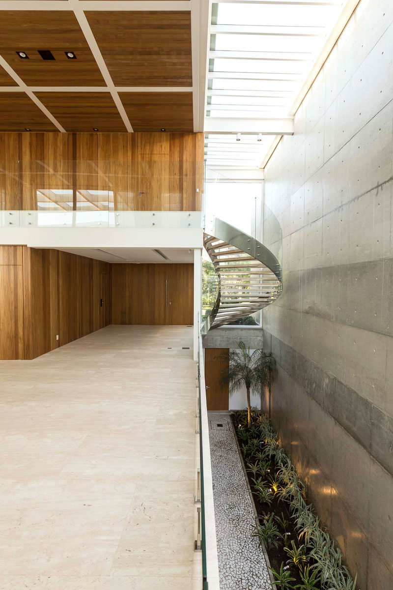 Stepping inside this modern house, there's an open hallway with a view of the stairs that lead to the upper floor, and a view of the large concrete wall found at the side of the house. #Stairs #Skylights #ModernHouse