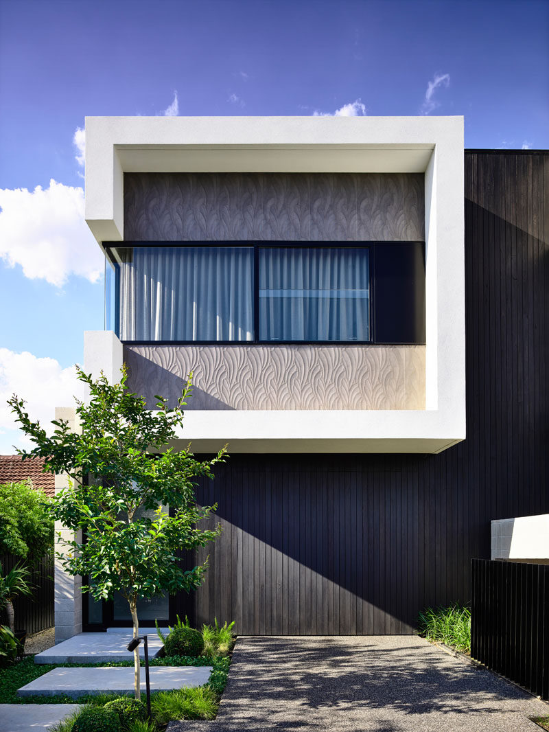 This modern duplex conceals the garages and utility room behind black stained vertical timber cladding