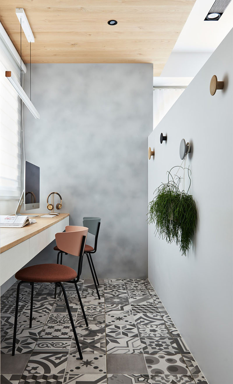 Hidden behind a pony wall in the living room of this apartment is a home office. Patterned tiles cover the floor while a wood ceiling adds warmth to the space. #HomeOffice #InteriorDesign