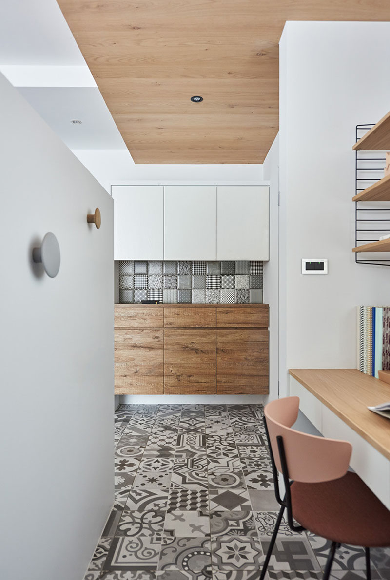 Hidden behind a pony wall in the living room of this apartment is a small home office. Patterned tiles cover the floor while a wood ceiling adds warmth to the space. #HomeOffice #InteriorDesign