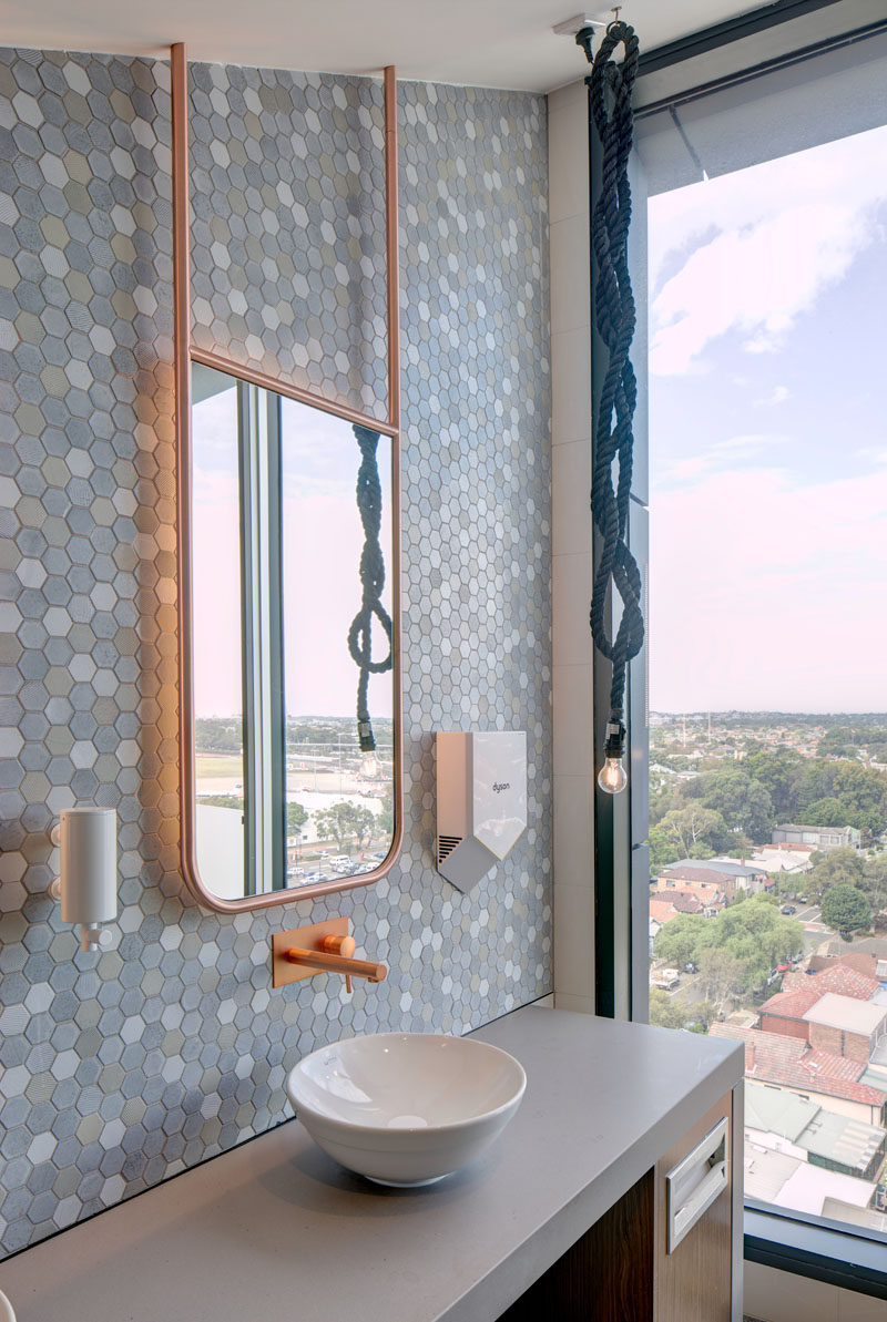 This modern bathroom has soft multi-colored hexagonal tiles as a accent wall, and a backlit copper framed mirror that hangs from the ceiling. #Bathroom #ModernBathroom