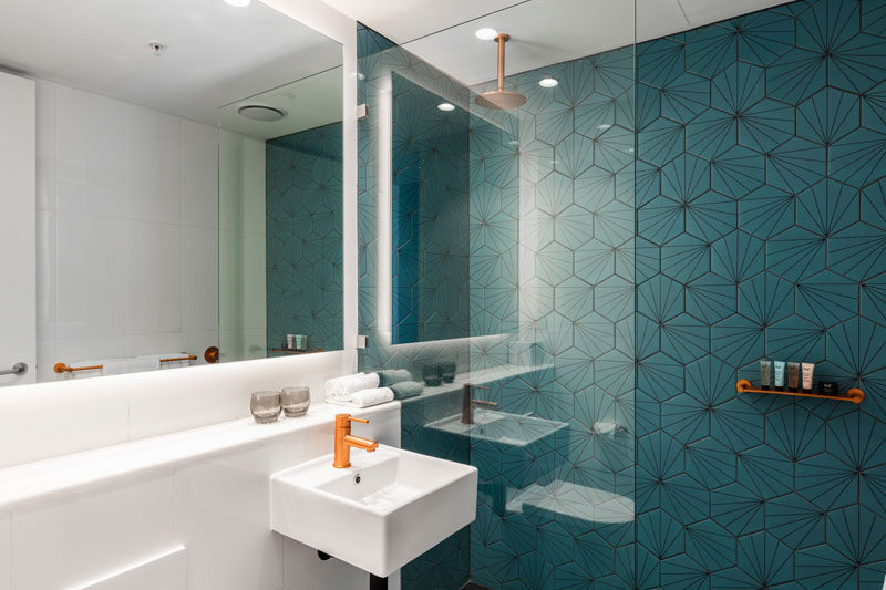 This modern bathroom features a dark turquoise, patterned accent wall in the shower, while a backlit mirror helps to keep the space bright. #Bathroom #AccentTile