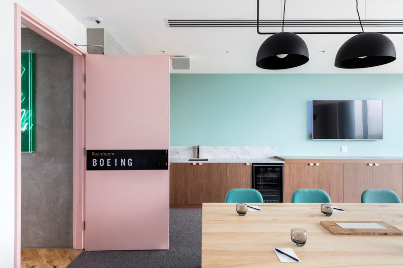 This hotel meeting room has a pale pink door that leads into a space with pastel blue walls and a bar/sideboard/kitchen area. #MeetingRoom #HotelInterior