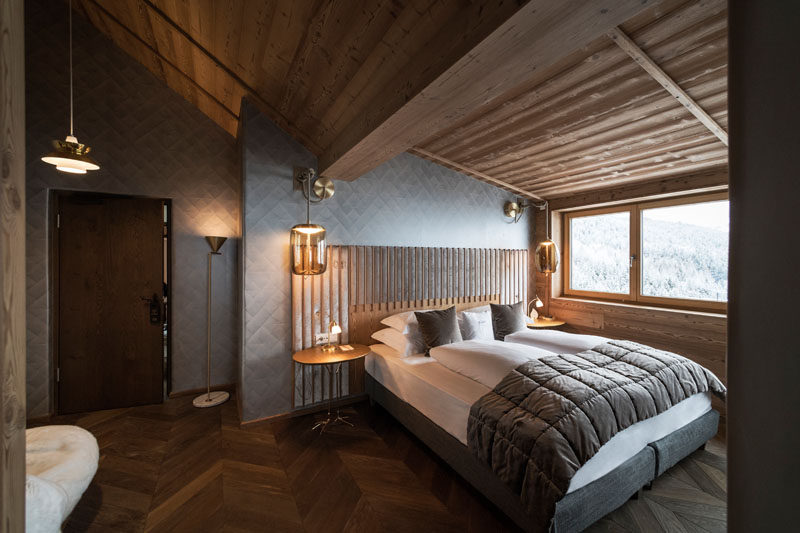 In this modern hotel room, bed sits against an almost metallic accent wall and beside the window, allowing guests to see outside without having to get out of bed. #AccentWall #Bedroom #HotelSuite
