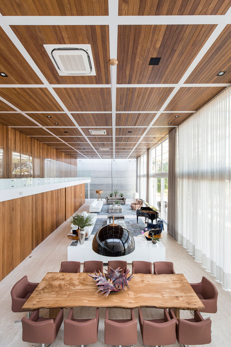 This modern house has a large double height living room and dining room. The kitchen and a home theater are hidden behind sliding wood doors. #LivingRoom #ModernInterior