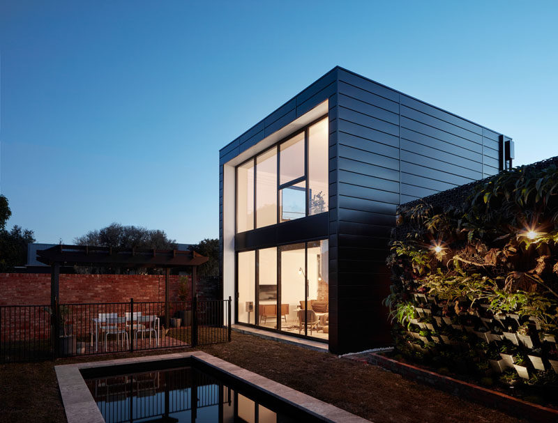 Modscape have designed a modern extension that includes an open living/dining/kitchen space, white spiral stairs, double height wall of windows and a mezzanine master suite. #ModernExtension #Architecture