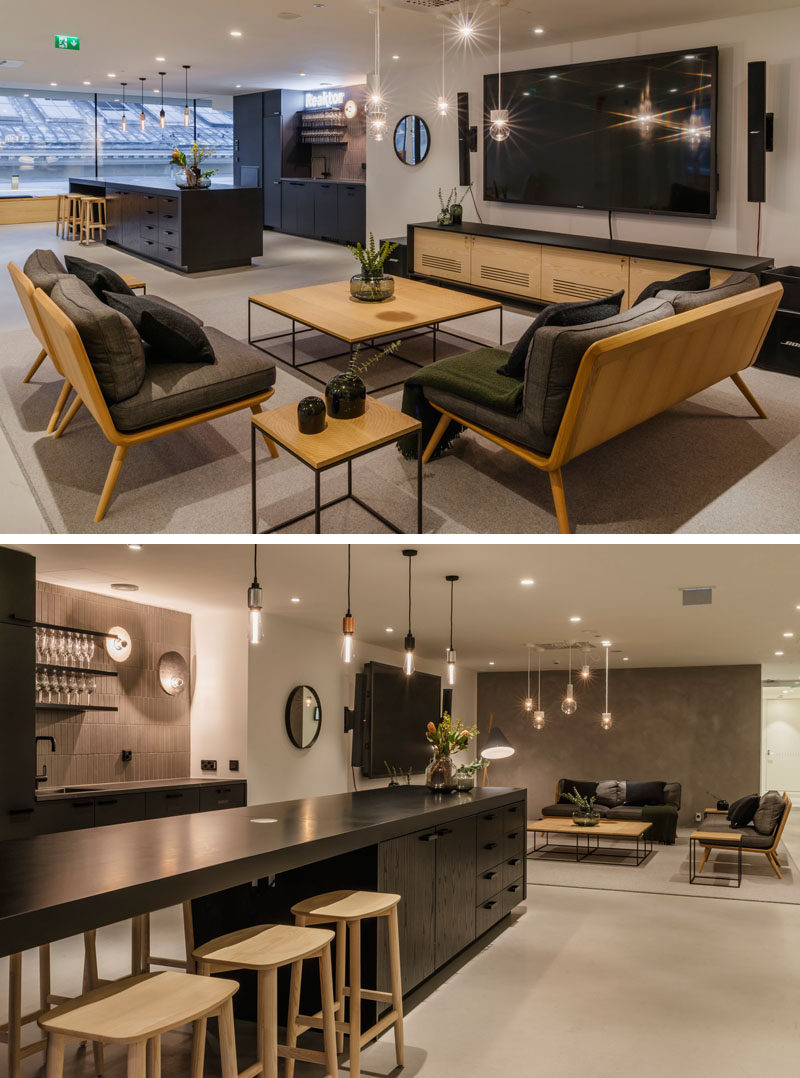 This modern offices features a dark kitchen with a long island, and a separate 'living room' like area for employees to relax. #Workplace #Kitchen #OfficeDesign