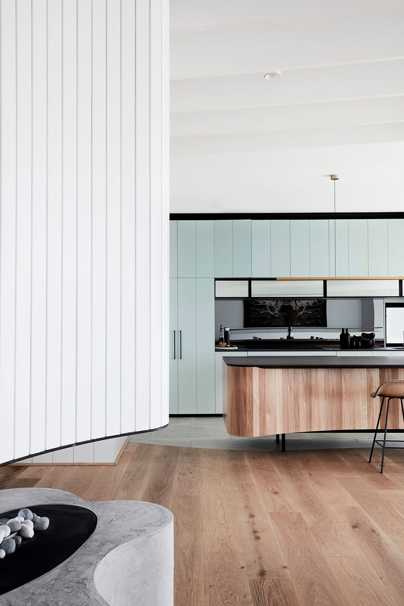 In this modern kitchen, light blue cabinetry byBuilding With Options has been combined with a reconstituted stone benchtop and an island covered with vertical wood pieces. #ModernKitchen