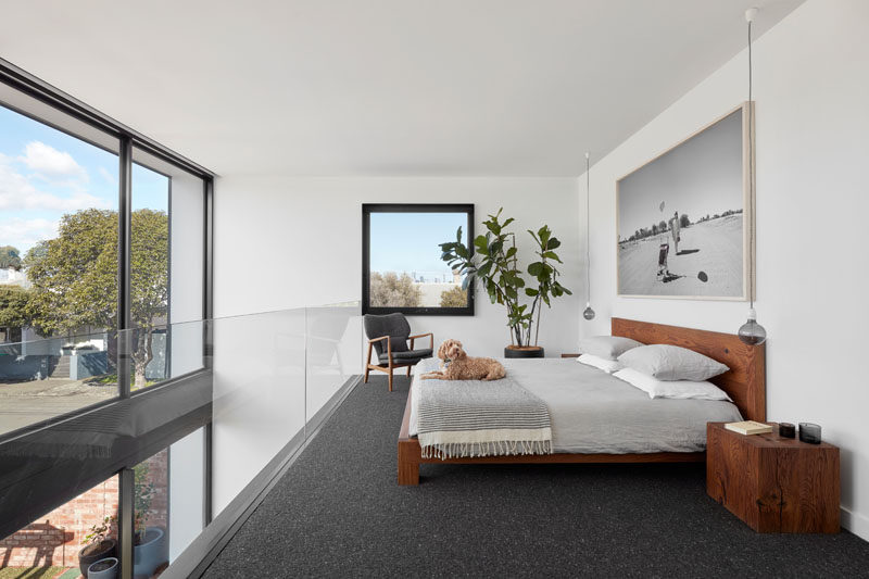 This modern mezzanine bedroom has the city's skyline is framed perfectly and sits like a picture on the wall, while a glass balcony allows seamless views of the backyard the neighborhood. #MezzanineBedroom #Windows