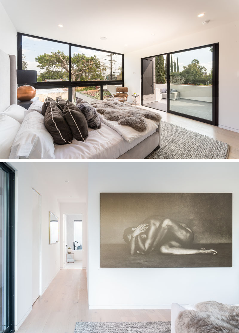 This modern master bedroom suite has a wall of windows that look out to the green roof and pool below. A hallway beside the bedroom leads down to the bathroom. #Modern #MasterBedroom