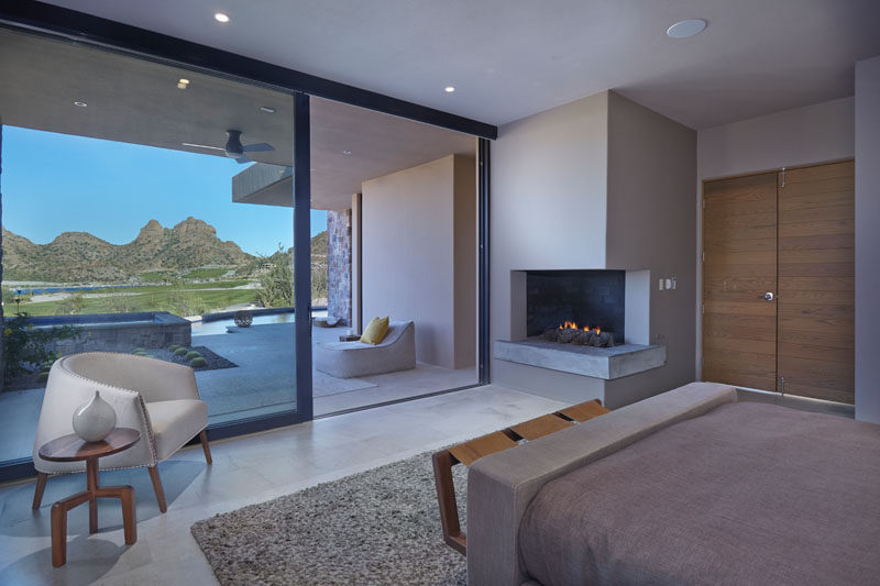 There's a corner fireplace in this modern master bedroom, and a sliding glass door opens up to a patio. #CornerFireplace #MasterBedroom #SlidingGlassDoor