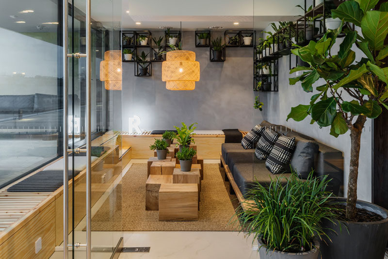 This modern meeting room has a dark couch, a wrap around bench and plenty of plants. #Workplace #MeetingRoom