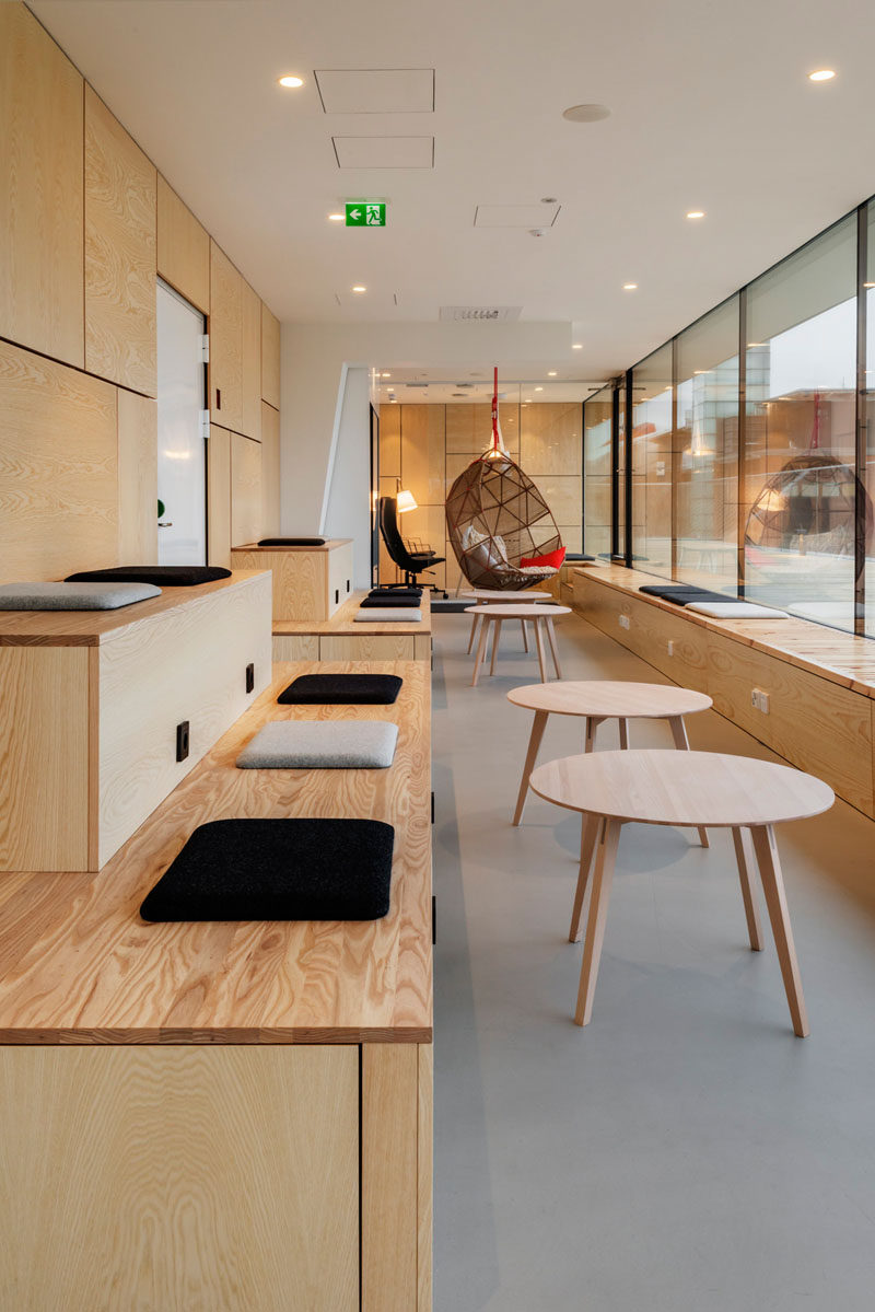 This modern office has tiered seating and benches to let the employees have a place to sit and work while enjoying sun through the windows. #TieredSeating #Workplace #OfficeDesign