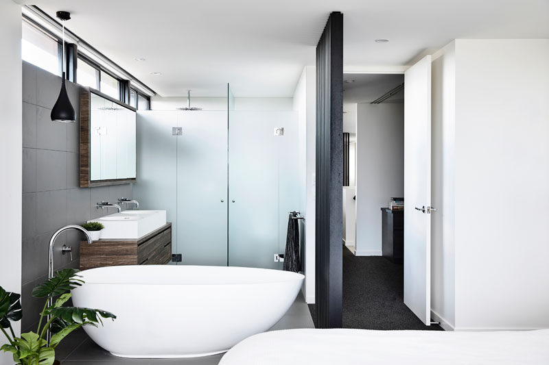 In this modern bedroom, the bathroom is located within the room and is open, with only the shower and toilet behind closed doors. #Bathroom #ModdernBedroom