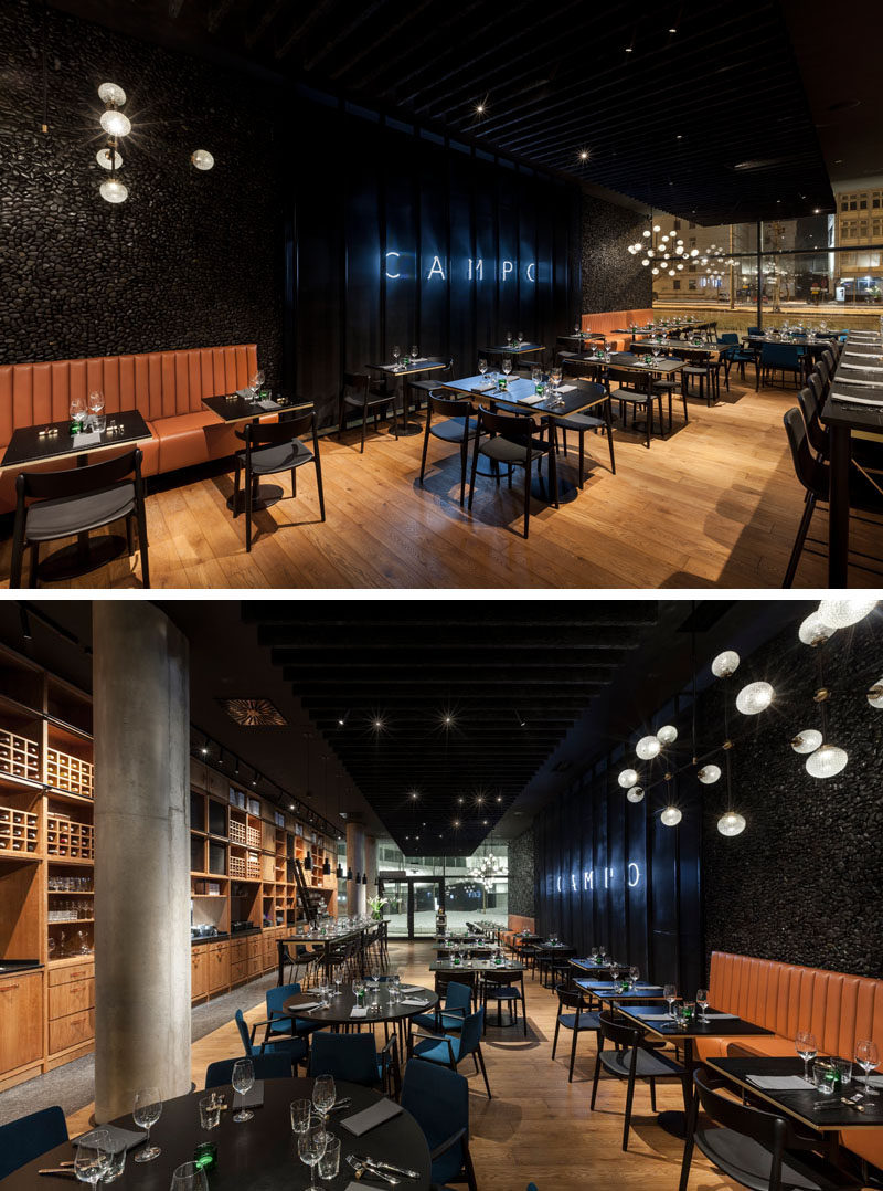 This modern restaurant features an open plan dining room, withdark colors and natural materials, like wood, leather and stone. #ModernRestaurant #RestaurantDesign