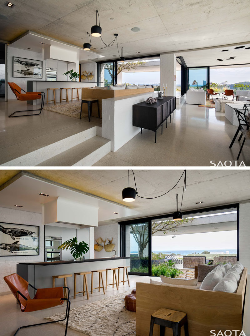 The kitchen and lounge area is at the center of the living space in this modern house, with a sofa in the kitchen large enough to seat the entire family. #ModernKitchen #ModernInterior