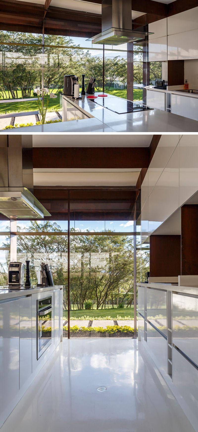 This modern kitchen has minimalist white cabinets that match the white floor. #WhiteKitchen #Windows