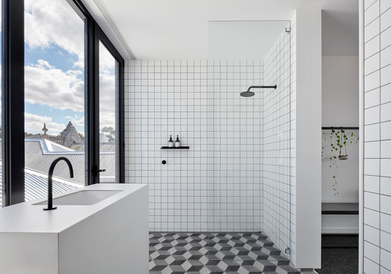 This bathroom features Marca Corona hexagonal tiles on the floor, and simple white square tiles with a dark grout on the walls. Matte black bathroom fixtures complement the window frames and create a modern appearance. #ModernBathroom #BathroomDesign
