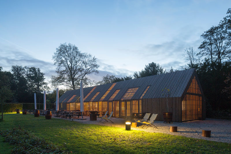This modern barn-like building nine movable facade parts that open up the building in the morning and close it at night. #Barn #Architecture #BuildingDesign