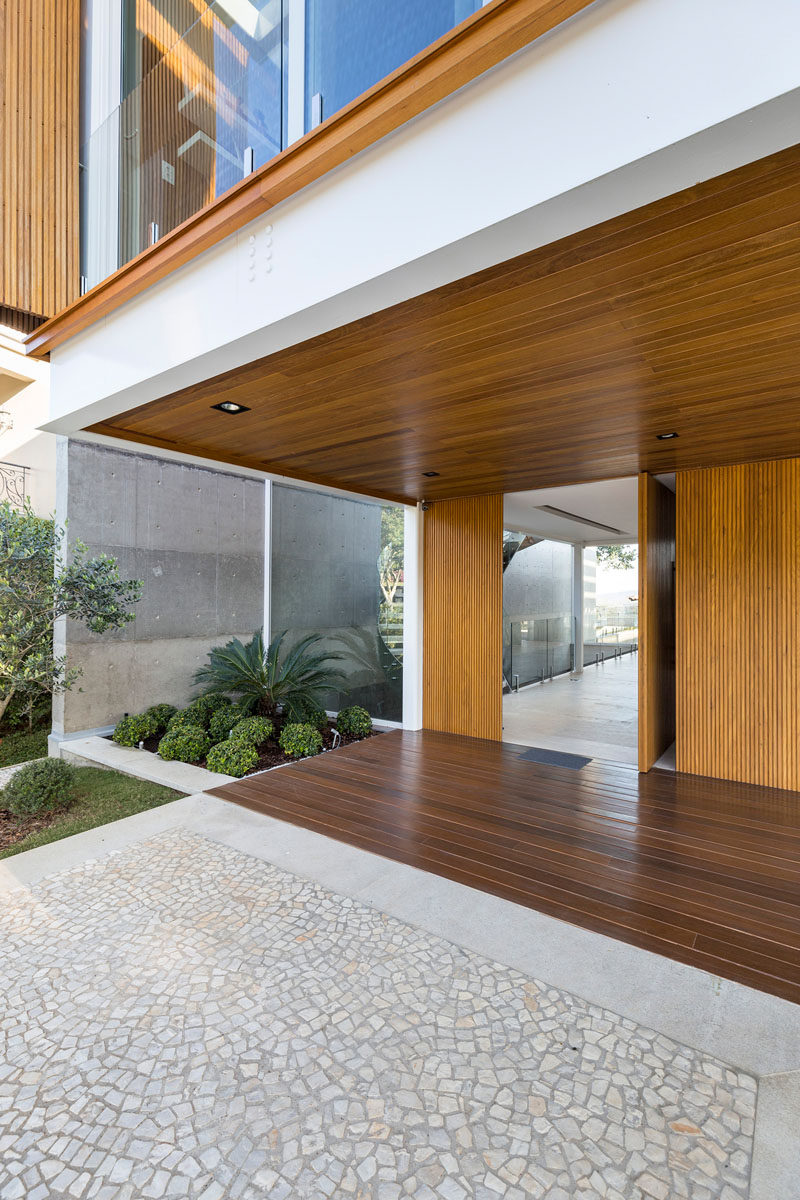 This modern house has a pivoting wood front door that matches the wood used on the upper level of the home. #ModernFrontDoor #WoodFrontDoor #PivotingFrontDoor