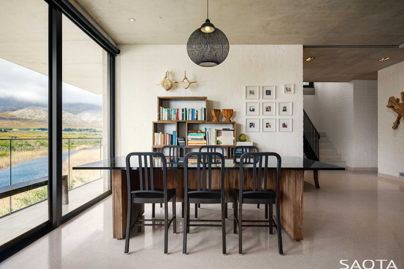 This modern house has a table that sits next to a bookshelf, making it the perfect spot for reading or playing games. #GamesRoom #InteriorDesign