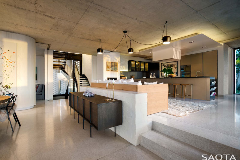 This modern house has a the kitchen and a couch raised up from the dining area. #InteriorDesign #Kitchen