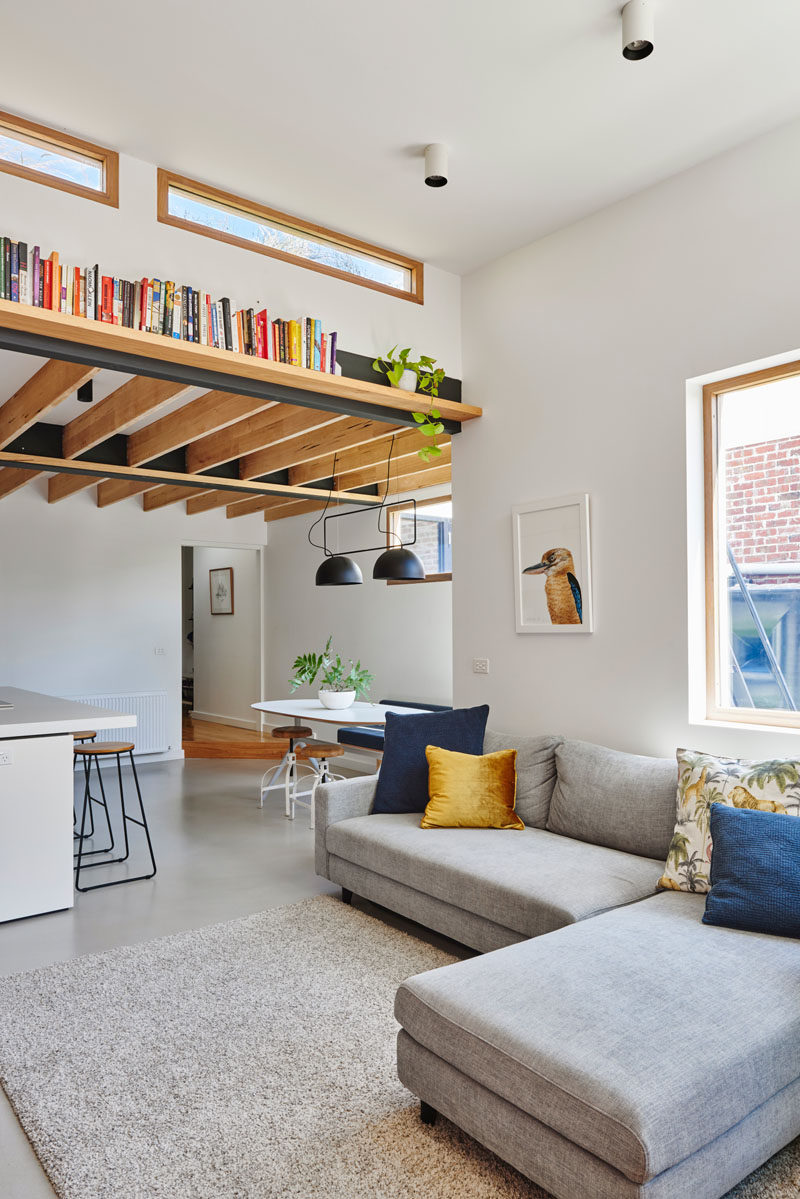 This modern living room has been set up with a simple grey couch and matching rug. A wood book shelf that's affixed to a beam draws the eye upwards to the height of the room and the windows. #LivingRoom #Shelving