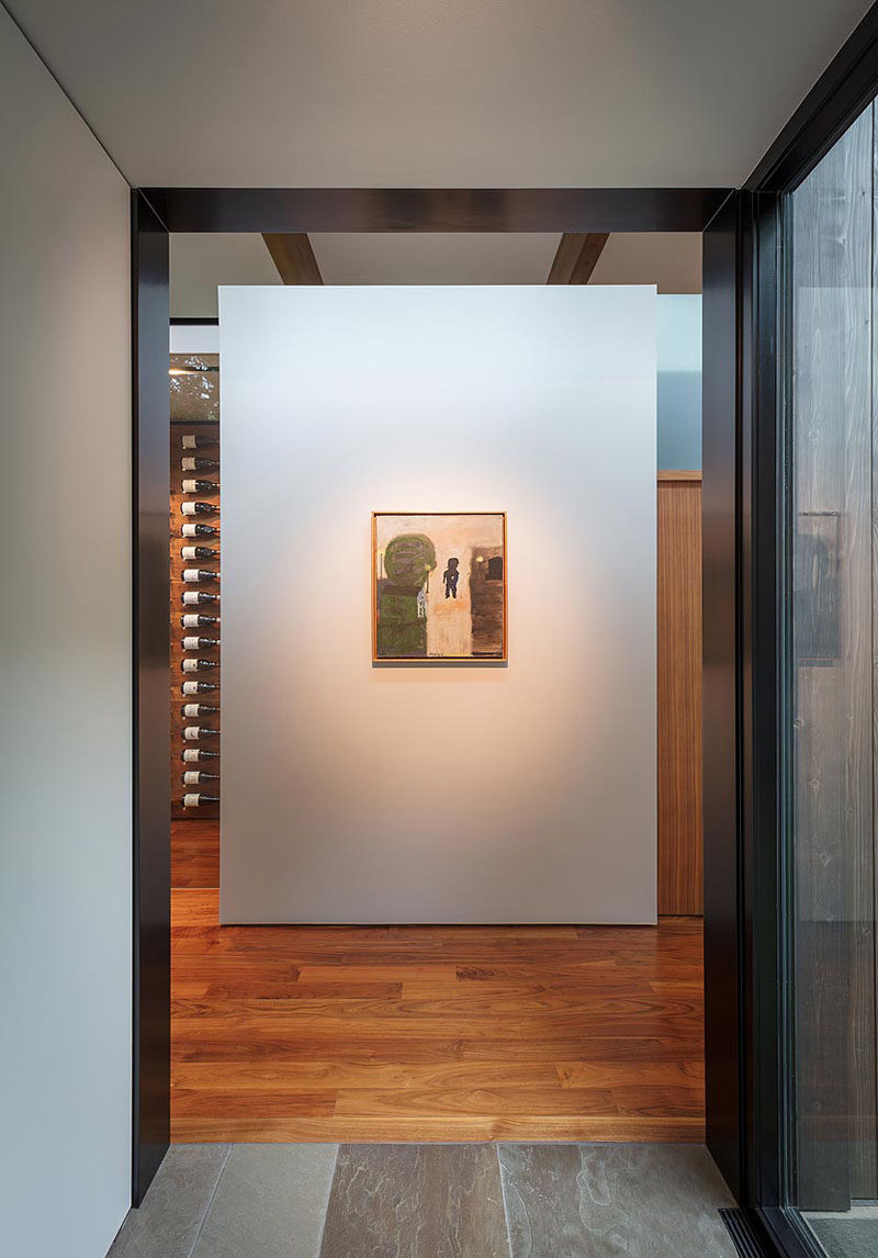 At the end of a hallway in this modern house, there's a single piece of artwork that's highlighted. #InteriorDesign