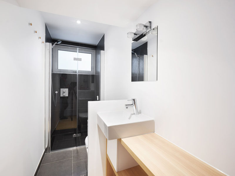 This small bathroom has a glass enclosed shower with dark tiles, and a small partition wall separating the vanity area from the toilet. #SmallBathroom #BathroomDesign