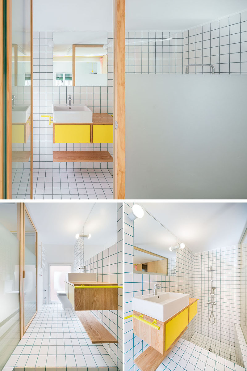 A partially frosted glass wall allows light to travel through to this long and narrow bathroom, however it also provides a degree of privacy. At one end of the bathroom is the toilet, while the other end is dedicated to a sunken bathtub and shower. #Bathroom #ModernBathroom