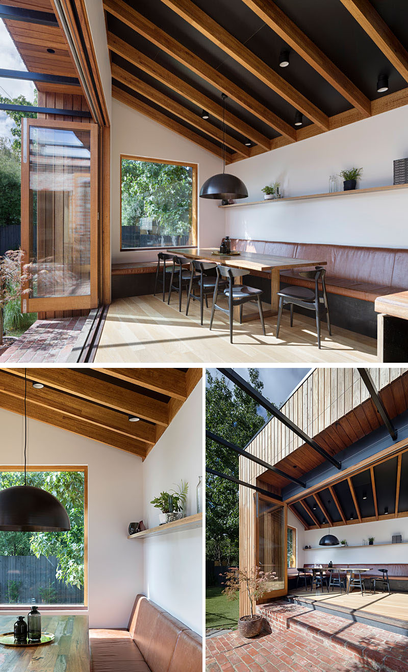 This contemporary house addition features restaurant style banquette seating that extends from the kitchen bench, while a large window provides views of the trees. Click through to see more photos. #BanquetteSeating #BanquetteDining #DiningRoom