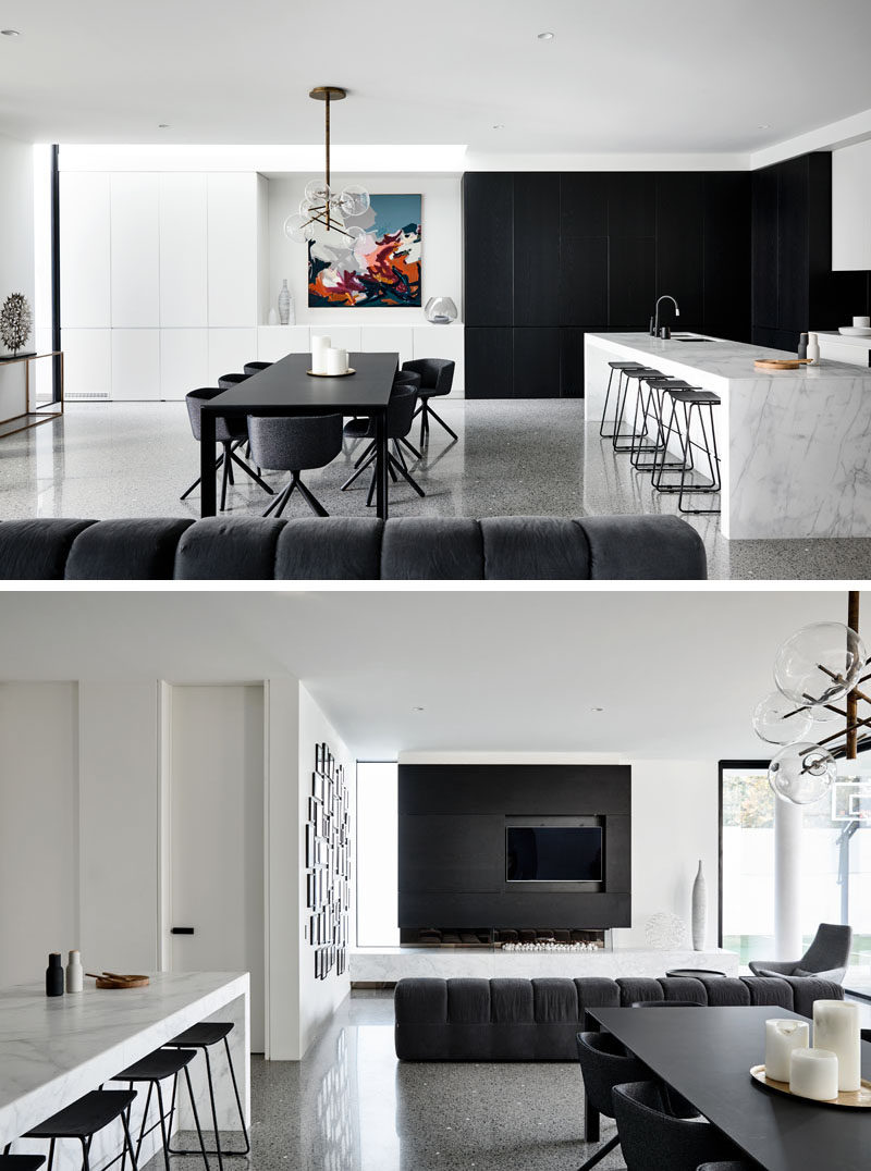 This modern house has an open plan living room, dining room and kitchen, that all follow a black and white color palette. Click through to see more photos of this modern house. #BlackDiningRoom #BlackAndWhite #InteriorDesign #ModernInterior #BlackAccentWall