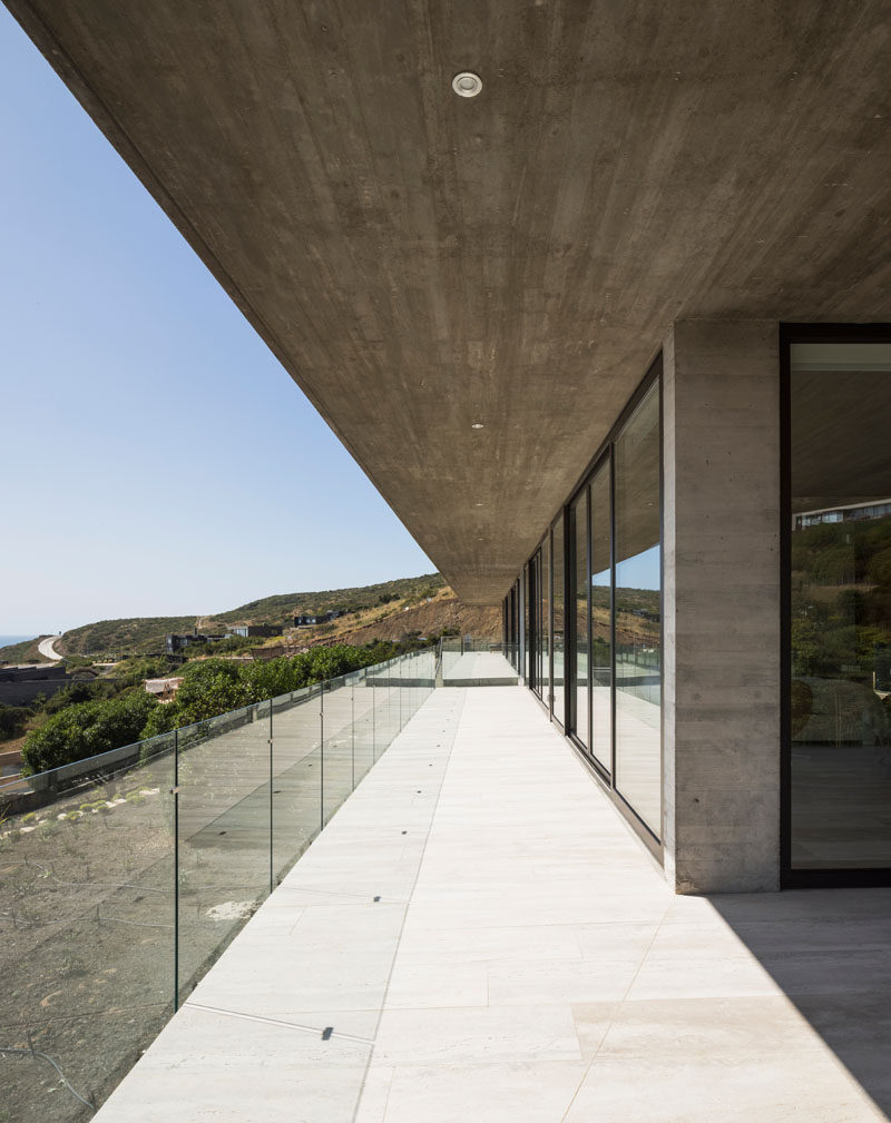 Sliding glass doors open all of the rooms of this modern concrete house onto the balcony. Click through to see more photos of this house. #Balcony #GlassRailing #ConcreteHouse