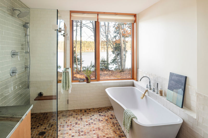 In this master bedroom, the bath is positioned to take advantage of the views. A walk-in shower with a glass surround helps to keep the bathroom feeling open and bright. #MasterBathroo #BathroomDesign