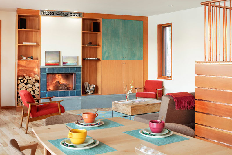 Materials like copper, tile, and wood have been used throughout this contemporary living room. #Fireplace #LivingRoom #BuiltInShelving