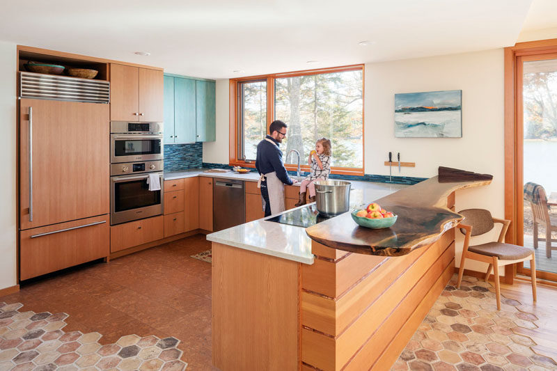 In this U-shaped kitchen, a live edge bar sits next to the countertops, while beside the kitchen are doors that lead to the deck with water views. #WoodKitchen #KitchenDesign