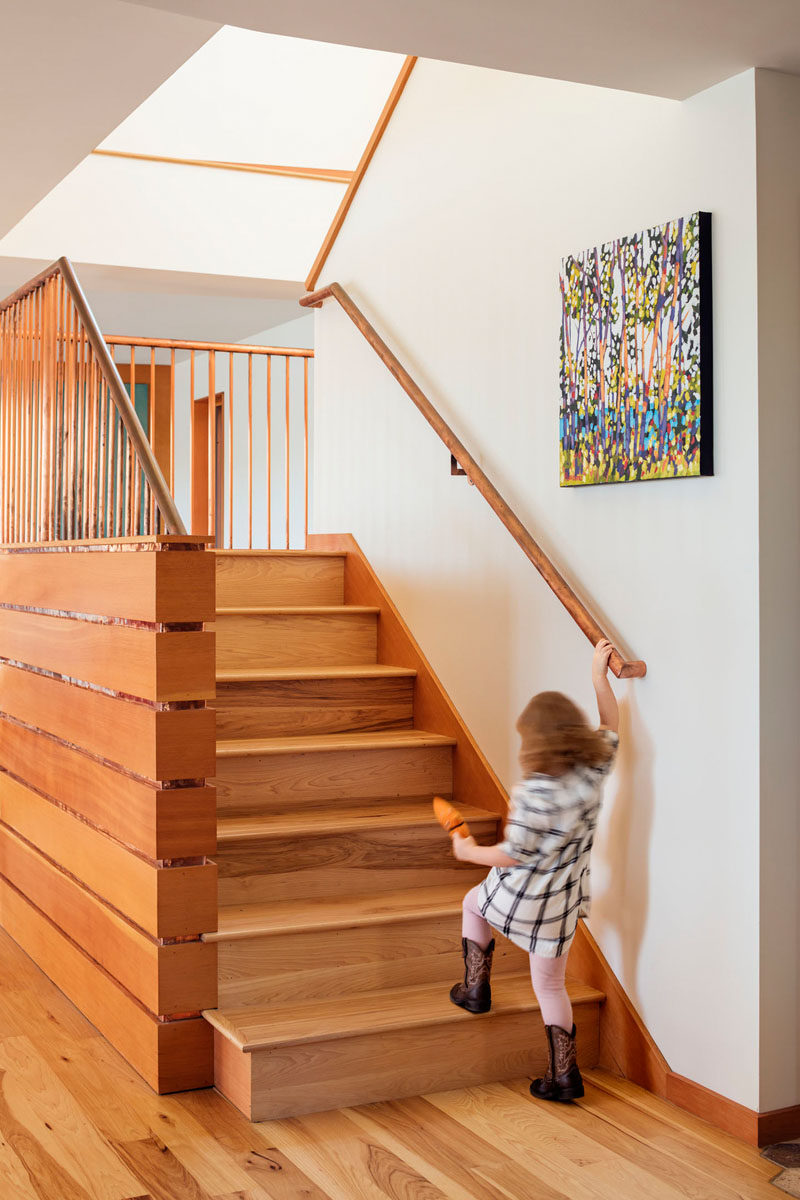 Simple contemporary wood stairs with a wood handrail connects the floors of this house. #WoodStairs