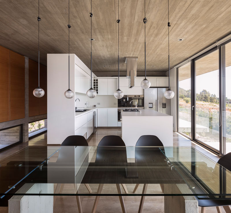 This glass, steel and concrete dining table is anchored in the room by the use of 6 pendant lights that hang from the ceiling. Click through to see more photos of this concrete house. #DiningRoom #InteriorDesign #WhiteKitchen