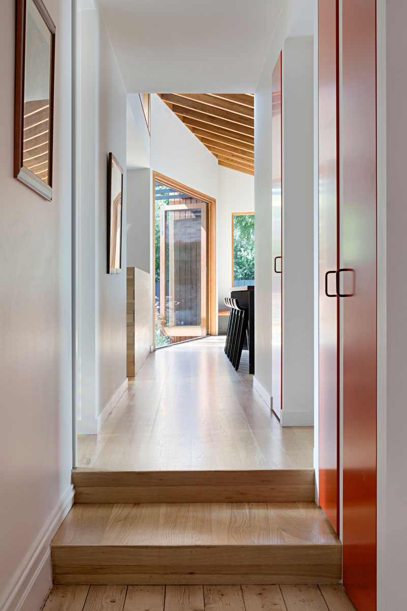 Connecting the original house with the new addition is a hallway with a wood floor that provides access a bathroom and a laundry room. #Hallway #WoodFllor