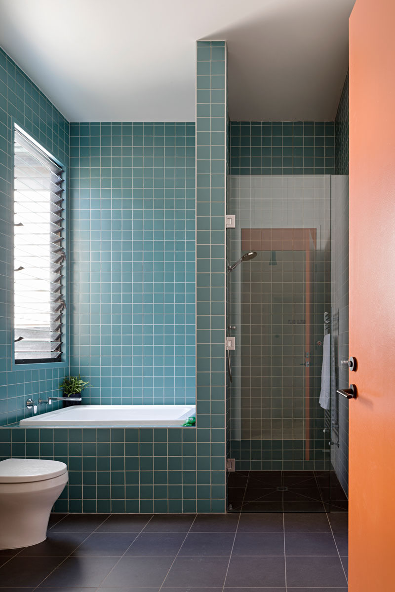 In this modern bathroom, there's a walk-in shower and a half-size bath that are surrounded by square blue tiles with a white grout. #BathroomDesign #SmallBathtub #ModernBathroom #BlueTiles