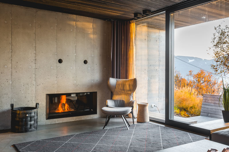 This modern living room has a concrete wall with a built-in fireplace, and a large sliding glass door opens to the outdoors. #ModernFireplace
